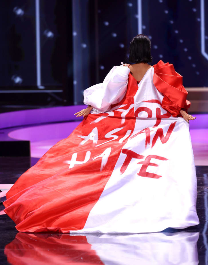 """Miss Universe Singapore Bernadette Belle Ong wears a Arwin Meriales x Paulo Pilapil Espinosa cape hand-painted with the hashtag """"#StopAsianHate."""" Credit: Rodrigo Varela/Getty Images"""